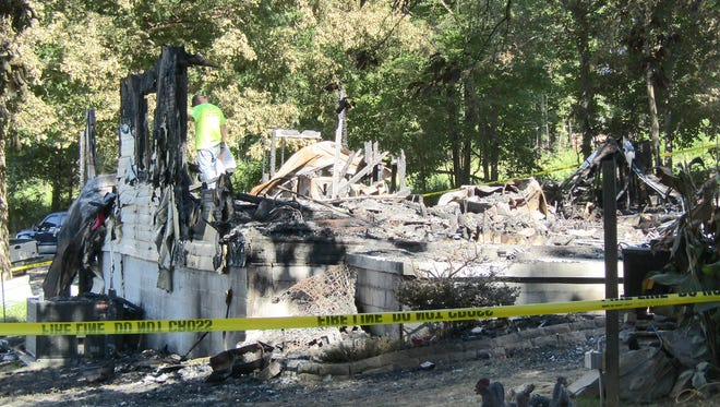 Family members and friends sift through ashes the remain after a fire destroyed the home in Fairview.