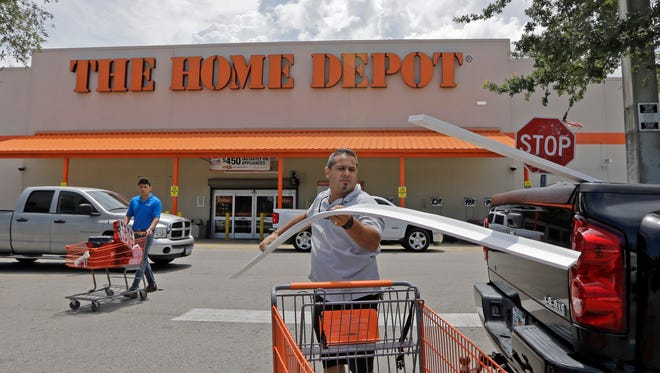 Vicente Aguiar loads garage door trims into his pickup truck outside a Home Depot in Hialeah, Fla., on July 13, 2015.