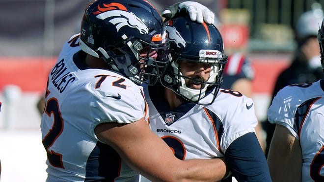 Denver Broncos offensive tackle Garett Bolles, left, congratulates kicker Brandon McManus in the second half of an NFL football game after his sixth field goal against the New England Patriots, Sunday, Oct. 18, 2020, in Foxborough, Mass.
