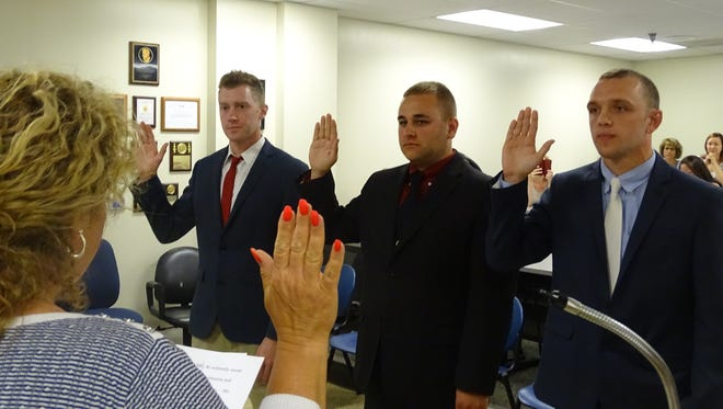Bryce A. Edwards, Cameron J. Shepherd and Nicholas A. Stevens are sworn in as probationary police officers for the Mansfield Police Department during a Friday ceremony.