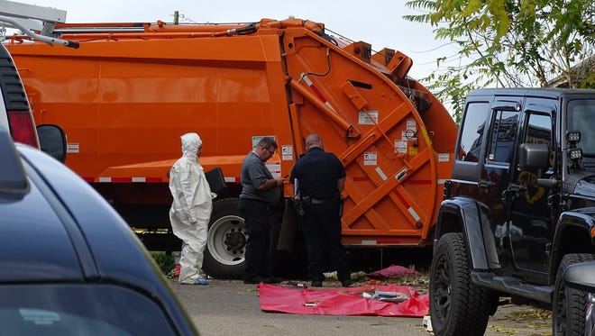 Officials stand outside 623 Glencroft Avenue Monday morning. Dressed in haz-mat suits, officials sifted through debris and trash in the home for hours before carrying a body outside around noon.