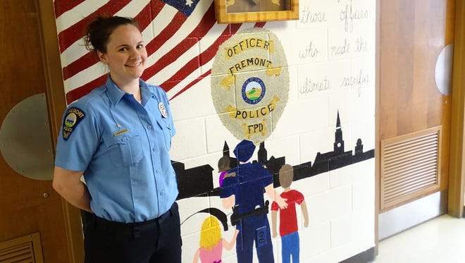 Katy Hasselbach, a Fremont Police Department dispatcher, stands next to a mural she painted at the department's main station. Hasselbach said she painted the mural over the span of a couple of weeks.