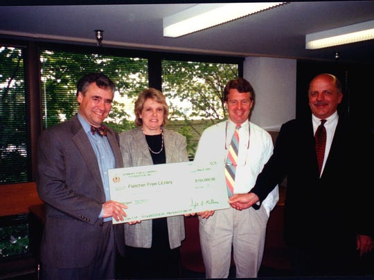 Burlington Mayor Peter Clavelle, right, and Fletcher Free Library Board President Geoffrey Crawford receive the library's first VT Public Library Foundation check from state librarian Sybil Brigham McShane and Don Post, Freeman Foundation representative in May of 2002.