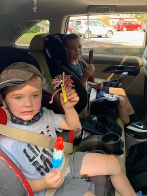 """Graedyn and his brother enjoying a frozen treat while showing off his """"Take It & Make It Craft,"""" sponsored by library staff."""