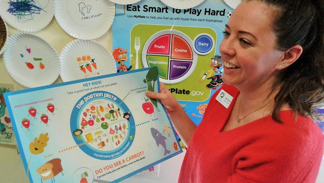 Executive Director Kaila Rome examines a placemat used to encourage healthy nutrition for kids at the North Liberty Community Food pantry.  On the wall are paper plates children decorated with vegetable art at a booth operated by the pantry at the city's Blues & BBQ event last summer.