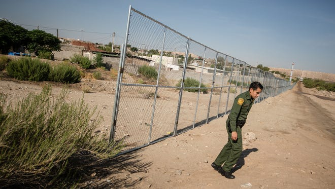 U.S. Border Patrol Agent Oscar Cervantes walks near the last remaining temporary fence along the U.S.-Mexico border near Sunland Park. The fence is being replaced by a taller, steel structure.