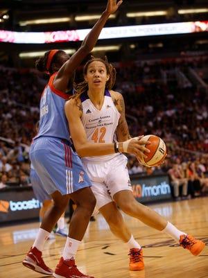 Mercury center Brittney Griner dips under the defense by Atlanta Dream forward/center Aneika Henry during the second quarter of their WNBA game at US Airways Center in Phoenix, Ariz. August 5, 2014.