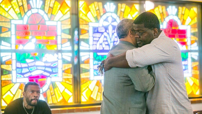 The Rev. Dr. Benjamin Thomas Sr. (middle left) embraces the Rev. Reginald D. Walton after a prayer service at Historic Tanner Chapel AME Church in Phoenix on Thursday, June 18, 2015.