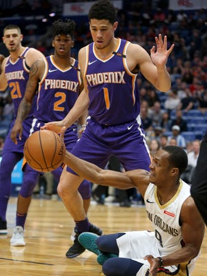 Feb 26, 2018; New Orleans, LA, USA; New Orleans Pelicans guard Rajon Rondo (9) falls down while defended by Phoenix Suns guard Devin Booker (1) in the first quarter at the Smoothie King Center. Mandatory Credit: Chuck Cook-USA TODAY Sports