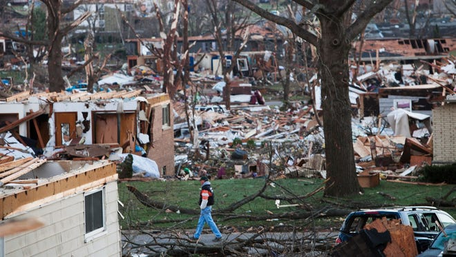 A man walks through what is left of a neighborhood in Washington, Ill., on Nov. 18, 2013, a day after a tornado ripped through the central Illinois town.