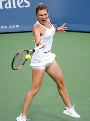 Simona Halep makes a hit to Angelique Kerber during