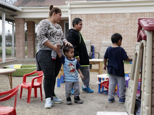 In this Jan. 11, 2019, photo, Maria Orbelina Cortez stands with her three sons, ages 11, 5, and 3, in the yard behind the Catholic Charities shelter in McAllen, Texas. Orbelina says that after fleeing El Salvador, she hopes to find refuge for her children with her parents in California.