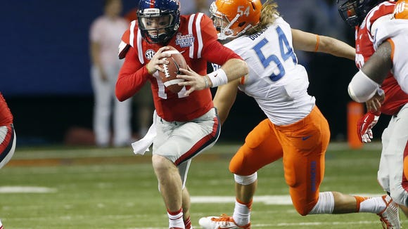 Mississippi quarterback Bo Wallace (14) runs past Boise State linebacker Mat Boesen (54) in the second half of an NCAA college football game, Thursday, Aug. 28, 2014, in Atlanta.  (AP Photo/John Bazemore)
