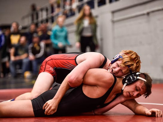 Ridgedale's Brandon Lewis, top, tries to gain the advantage over Pleasant's Reese Wolf during a match last season.
