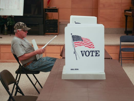 Dan Grandgenette of Corwith pours of the ballot for the special election where residents voted to dissolve the Corwith-Wesley School district on Tuesday, Sept. 9, 2014, in Corwith, Iowa.