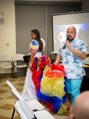 Filipino Community of Guam President Norman Analista describes a gown created by celebrity Filipino designer Ramon Santiago. The dress, modeled by Nadia Pablo, was inspired by the colors of the Philippine flag and it has a detachable train. This is one of the pieces that is available for purchase after the October 20 event.