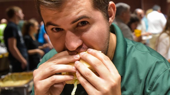 Pauly Domingue eats a po'boy at the 2016 Eat Lafayette kickoff event featuring local restaurants participating in the annual summer dining campaign.
