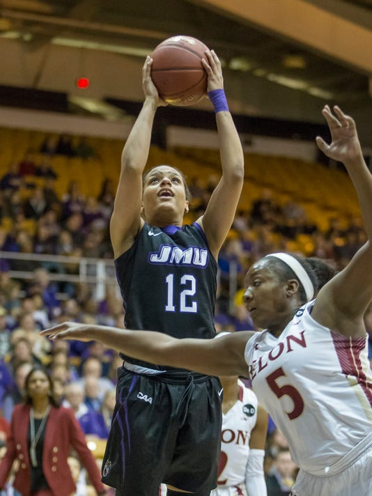 James Madison guard Precious Hall (12) drives to the basket past Elon guard Shay Burnett (5) during an NCAA college basketball game for the championship of the Colonial Athletic Association tournament in Harrisonburg, Va., Saturday, March 11, 2017. (AP Photo/Chet Strange)