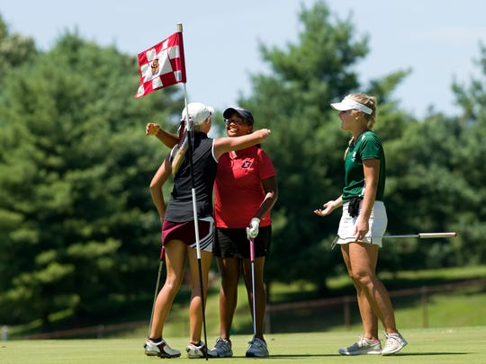 The threesome of (from left) Payton Carter, Henderson County, Ke'Asha Phillips, Owensboro, and Emiy Lyons, Owensboro Catholic finish up their round on the 18th green at the Henderson County Lady Colonels Invitational at the Henderson County Country Club Monday afternoon.