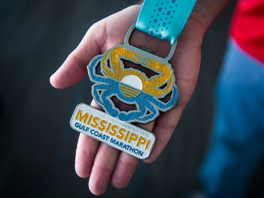 Rex Walter displays a medal from the group's Gulf Coast marathon on Dec. 15, 2016, in Hanover.
