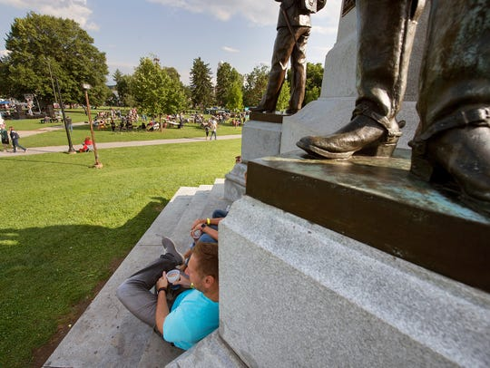 People relax at the feet of the York County Soldiers