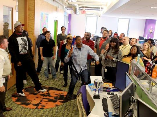 Team members at Quicken Loans gather as Sr. Client Care Specialist. Matt Canty, 38, (center) leads the troops on a spontaneous rally to help get any bad energy out so that team members can get back on their phone calls with a refreshed attitude on Friday, Oct. 10, 2014.