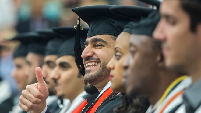 A graduate finds his family and friends in the crowd.