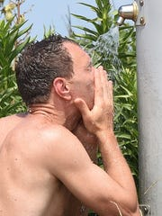 A visitor to Rehoboth Beach cools off with a cold shower.