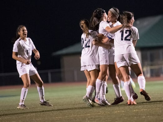 The Trojans celebrate after Lauren Ocker (5) scored
