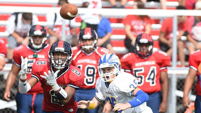 Roy C. Ketcham's Zahir Woody catches a pass as Mahopac's Anthony Ocello tries to catch up to him during Saturday's game at Ketcham.