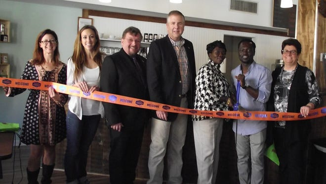 Participating in a ribbon-cutting ceremony to note the recent grand opening of Teylev Café and Lounge in Downtown Somerville are, left to right, Downtown Somerville Alliance Executive Director Beth Anne Macdonald, Mallori Seader, owner, Gems & Stems and Alliance board member, Council President Steve Peter, Mayor Brian Gallagher, Linda Bonsu, mother of Teylev owner Stephen Bonsu, who is pictured next to her, and Councilwoman Jane Kobuta.