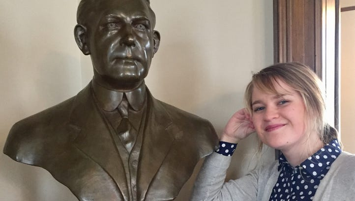 "Katrina ""Rena"" Sletten poses with a bust of Daniel"