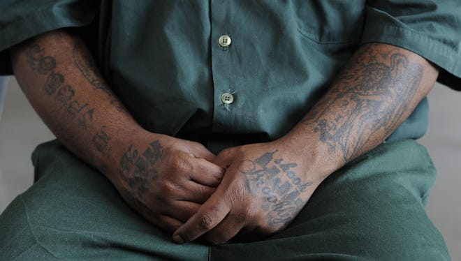 Lamont Pride, sporting tattoos, sits in a visiting room at Attica Correctional Facility in Attica, N.Y.