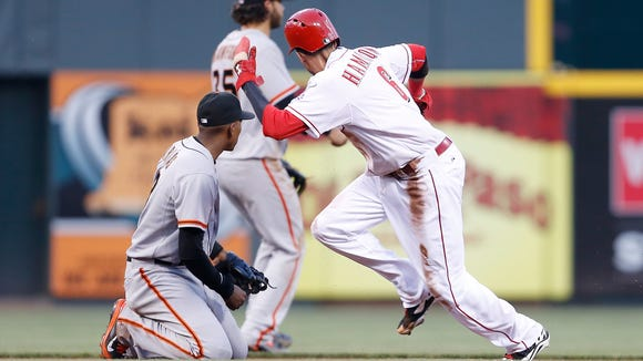 Billy Hamilton (6) heads to third base after a throwing error by Giants catcher Hector Sanchez (29) in the fifth inning.