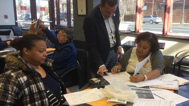 Paterson Deputy Mayor Danilo Inoa assists Wendy Sosa and her sister Gleny Sosa, both of Paterson,  with their U.S. Citizenship application at a workshop at Passaic County Community College on Saturday.