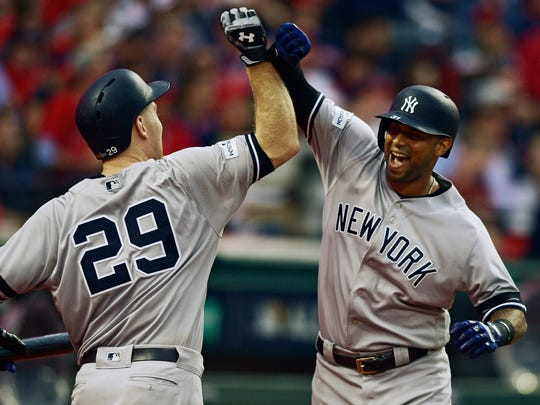 New York Yankees' Aaron Hicks, right, is congratulated by Todd Frazier after Hicks hit a three-run home run during the third inning of Game 2 of baseball's American League Division Series, Friday, Oct. 6, 2017, in Cleveland.