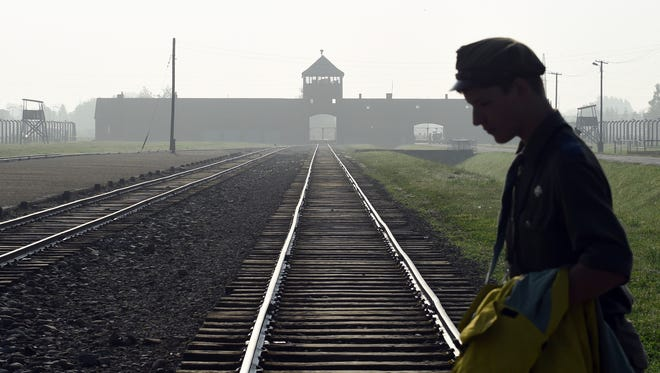 FILE - In this July 29, 2016 file photo a man crosses the rails leading to the former Nazi death camp of Auschwitz-Birkenau prior to a visit by Pope Francis, in Poland.