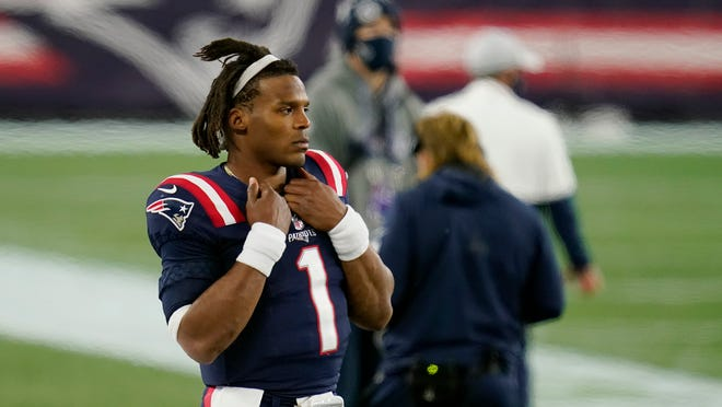 Patriots quarterback Cam Newton watches from the sideline after being replaced by Jarrett Stidham in the second half on Sunday.