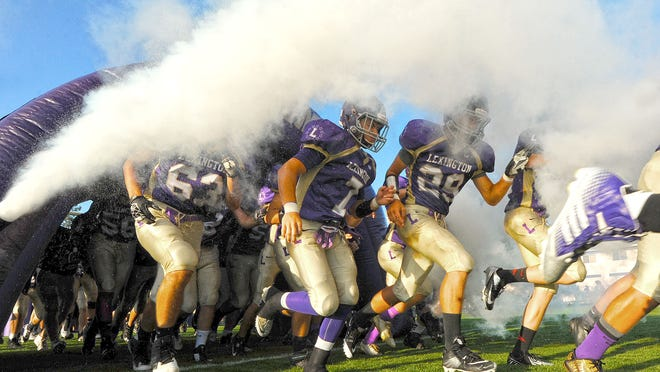 Members of the Lexington Minutemen football team take the field before a game earlier this season with Ontario.