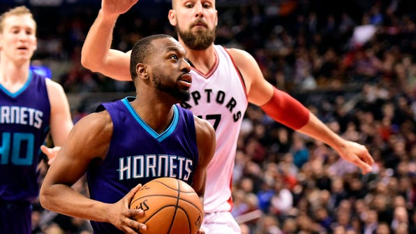 Charlotte Hornets guard Kemba Walker (15) drives to the net past Toronto Raptors center Jonas Valanciunas (17) during second half NBA basketball action, in Toronto on Wednesday, March 29, 2017. (Frank Gunn/The Canadian Press via AP)