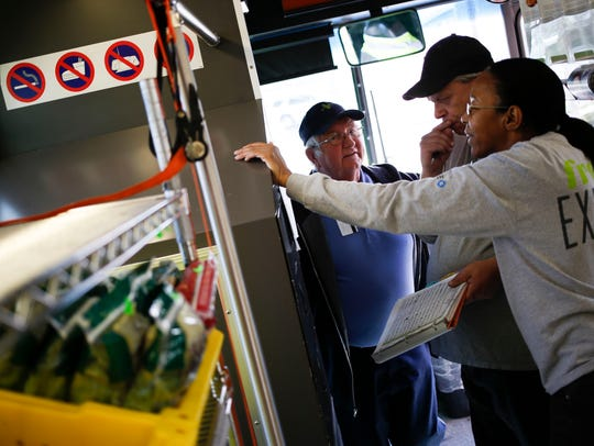 Staff on the Fresh Express bus chat as customers shop