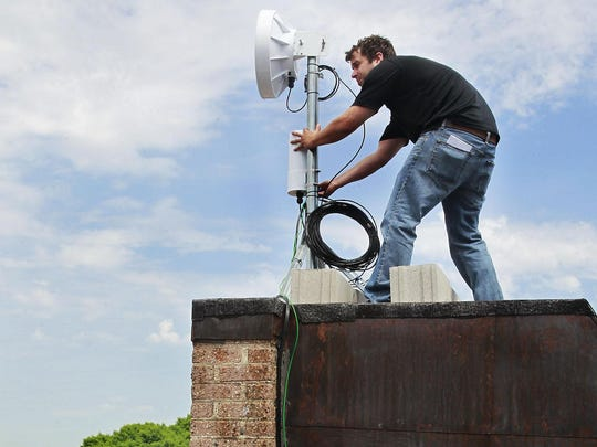 Pete Rein, field service manager for Ethoplex, a local internet service provider, makes adjustments to equipment on the roof of Cedar Square Apartments in Milwaukee on N. 15th St. in this file photo. Ethoplex provides gigabit service to Milwaukee-area homes.