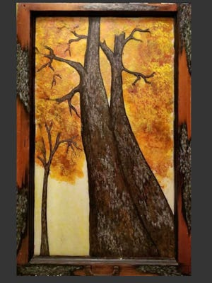 A dramatic painting of a tree in autumn is made more interesting by the artist making sections of the frame look like tree bark. The painting is on a discarded window. The handle to pull the window up can be seen at the bottom.