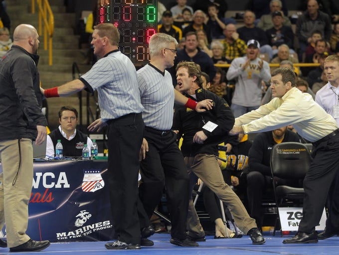 Iowa head coach Tom Brands holds back his brother,