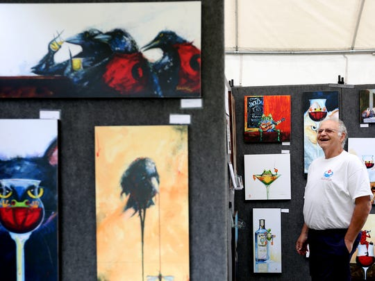 David Sterling, 61, of Ft. Worth, Texas, laughs while looking at paintings by the artist Barton DeGraaf during the 67th annual Salem Art Fair and Festival at Bush's Pasture Park in Salem on Saturday, July 16, 2016. The event continues on Sunday from 10 a.m. to 5 p.m.
