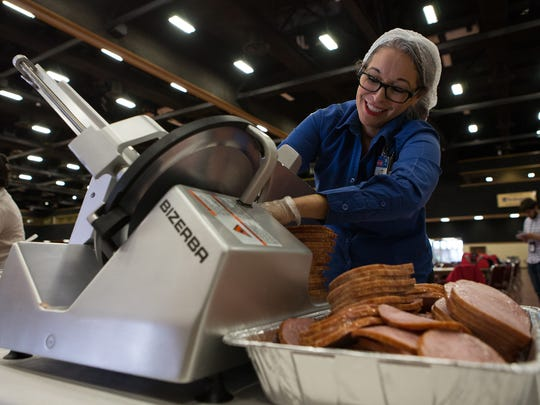 Liz  Saenz slices ham Friday morning as they are prepared for HEB's Feast of Sharing at the American Bank Center on Saturday, December 24.