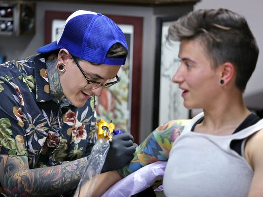 Dane Smith, left, adds color to Katie Shields' tattoo