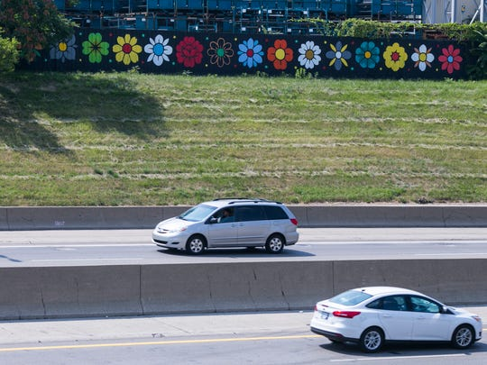 """A recent piece by local muralist Louise """"Ouizi"""" Jones, 29, is seen along the southbound service drive wall of I-75 in Detroit on Tuesday, August 8, 2017. The piece is part of a new program hiring local street artists to create murals in high visibility locations across the city of Detroit. (Brittany Greeson, Special to the Free Press)"""