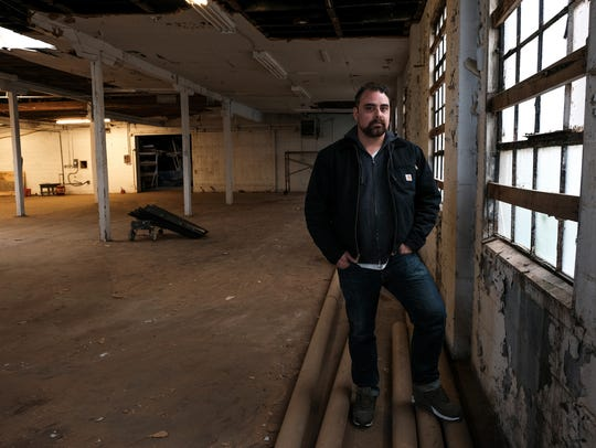 Jesse Cory, CEO of 1xRun, stands in a warehouse space in Detroit that will be the new location of the printmaker.
