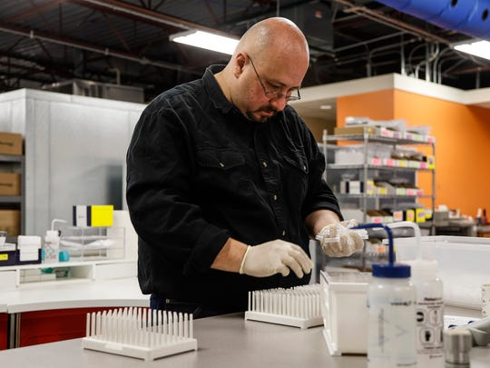 Jack Gross, manufacture assistant, sets up containers to fill up a product at the Arbor Assays office in Ann Arbor, Thursday, November 9, 2017.